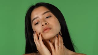 Studio portrait of a gorgeous Asian young woman posing sensually on green chromakey background. Sexy beautiful ethnic woman touching her face and neck gracefully. Sexuality, beauty concept.