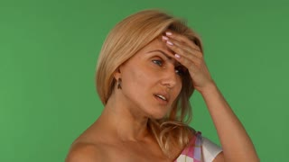 Studio portrait of a stunning mature woman breathing heavily, looking stressed and tired, posing on green chromakey background. Attractive woman looking exhausted.