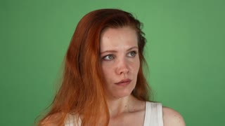 Studio portrait of a young red haired woman looking angry. Ginger female arguing with you, posing on green chromakey background. Conflict, emotions, misunderstanding concept.