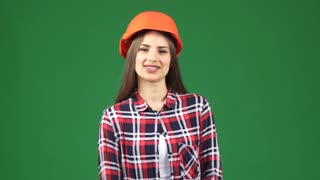 Studio shot of a beautiful cheerful young female construction worker engineer wearing protective hardhat smiling with her arms crossed on green chromakey background profession job builder.