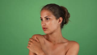 Studio shot of a beautiful young tanned woman with flawless skin, wearing no makeup, posing sensually on green background. Healthy gorgeous female looking to the camera.