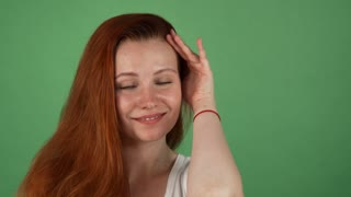 Studio shot of a beautiful young woman with long wavy ginger hair posing cheerfully on green chromakey background. Attractive red haired woman touching her face gently, copy space.