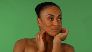 Studio shot of a gorgeous mature African woman with flawless skin touching her face sensually. Attractive mulatto female posing gracefully on green chromakey background.