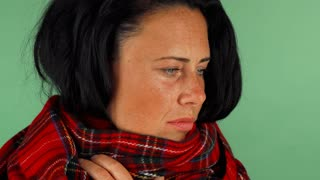 Studio shot of a mature woman wearing warm scarf, having a flu. Attractive female feeling sick, coughing on green chromakey background. Medicine, healthcare, virus concept.