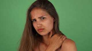 Stunning beautiful young woman looking upset, having upper back pain. Gorgeous female posing on green chromakey, feeling sick, rubbing her shoulder. Health, medicine, treatment concept.