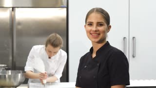 Stunning young beautiful female professional chef smiling joyfully to the camera showing thumbs up her colelague cooking at the kitchen on the background. Profession, employment.