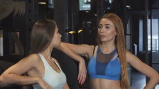 Stunning young red haired sportswoman talking to her beautiful female friend at the gym after working out together smiling to the camera showing thumbs up friendship health healthcare athletics