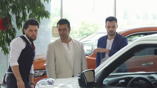 Three male friends examining cars for sale at the dealership showroom. Mature Hispanic man and his younger friends shopping for a new automobile. Communication, friendship, consumerism.