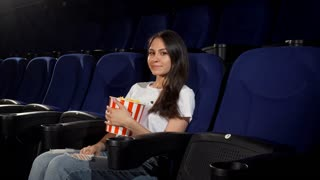 Young attractive woman pointing at the seat beside her at the movie theatre. Happy beautiful female spectator enjoying movies at the local cinema. Happiness, leisure, weekend concept.