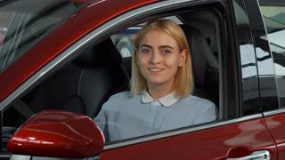 Young beautiful cheerful woman smiling to the camera while sitting in her new automobile. Happy female driver showing thumbs up holding car keys. Transportation, ownership concept.