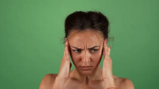 Young beautiful female looking nervous, rubbing her temples. Attractive woman having anxiety, posing green chromakey background. Stress, depression, worrying concept.