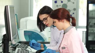 Young female laboratory workers using computer together conducting experiments at the modern lab. Two scientists working on a research. Science, development, technology, occupation, job.