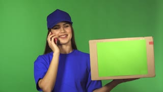 Young gorgeous delivery woman calling her client on the phone smiling joyfully delivering cardboard box package with a copyspace working with people transportation postal employee.