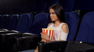 Young gorgeous happy woman holding her popcorn bucket, pointing at the cinema auditorium. Cheerful female spectator enjoying movies at the cinema. Holidays, youth concept.