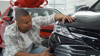 Young handsome African man smiling to the camera showing thumbs up, while examining an automobile for sale at the local dealership. Male customer choosing new auto to buy. Driving concept.