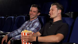 Young handsome man laughing joyfully talking to his friend while watching comedy movie at the cinema. Cheerful male friends eating popcorn at the movie theatre. Entertainment concept.