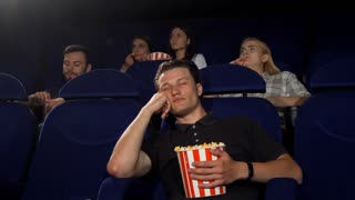 Young handsome man looking bored and tired sitting at the movie theatre. Attractive male spectator falling asleep at the cinema. Tired man watching movies. Entertainment, lifestyle concept.