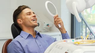 Young handsome man sitting in a dental chair examining his teeth. Attractive man smiling happily to the camera after dental examination at the dentist office. Teeth care, perfect smile concept.
