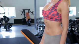 Woman alternately lifts dumbbells at the gym