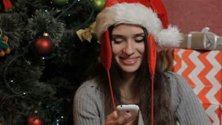 Woman calls on the phone near the christmas tree