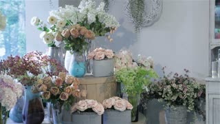 Woman chooses between tea-rose and pink rose at flower shop