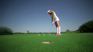 Woman hits three balls at the golf