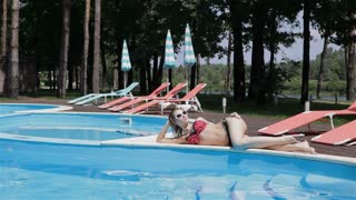 Woman lies on the opposite side of the swimming pool
