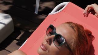 Woman lying in the sun near the swimming pool