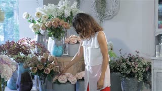 Woman picks one rose from the vase at flower shop