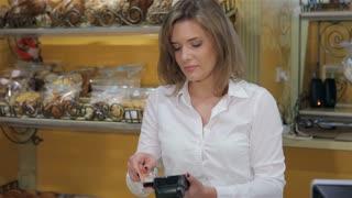 Woman processing credit card through the payment terminal
