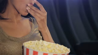 Woman puts her fingers on popcorn at the movie theater