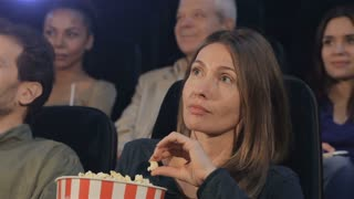 Woman puts popcorn into her mouth at the movie theater