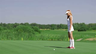 Woman stands on her knee at the golf
