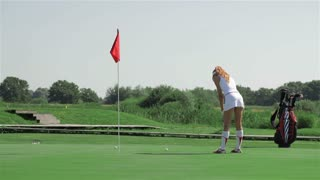 Woman stroke the ball into the hole at the golf