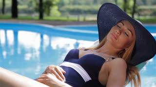 Woman sunbathes near the swimming pool