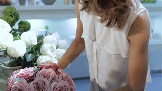 Woman takes a bouquet of pink roses at flower shop