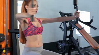 Woman trains her chest muscles on pec deck machine at the fitness centre
