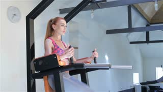 Woman trains lower abdominal muscles at the fitness centre