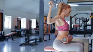 Woman trains on lat pull-down machine at the fitness centre