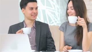 Young attractive business man and woman drink coffee and smile for discussion collating data