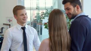 Young blond salesman shaking hands with customer at the car dealership. Caucasian sales manager in white shirt and black tie dealing with clients. Man and woman standing backwards against background