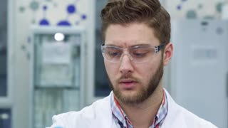 Young brunette man looking at the test-tube at the laboratory. Close up of atractive male scientist frowning. Brunette caucasian lab worker examining some test