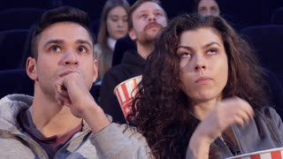 Young caucasian couple watching horror at the movie theater. Handsome brunette guy and his pretty girlfriend looking afraid. Close up of attractive boy and girl spending time at the cinema