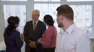 Young caucasian guy looking at business people at the office. Attractive bearded man standing against background of officially dressed senior man and two mature women. Handsome brunette businessman in