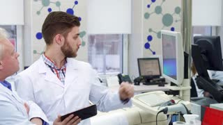 Young caucasian man comparing data on computer and tablet. Attractive bearded intern pointing his forefinger on monitor screen at the laboratory. Gray senior lab worker noding near his colleague