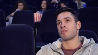 Young caucasian man getting bored at the movie theater. Close up of brunette boy watching dull film. Attractive guy leaning his head on his hand at the cinema