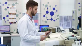 Young caucasian man in white coat entering information from computer to the tablet. Attractive male scientist standing in front of computer with tablet in his hands. Brunette bearded intern using