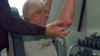 Young caucasian trainer helping senior client during the training. Close up of bearded guy standing behind the old sportsman. Fit brunette man holding his hands under the elbows of aged man