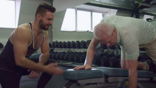 Young caucasian trainer watching how senior client doing the exercises at the gym. Attractive bearded guy standing on his knee near the old gray man. Brunette male fitnes specialist advising aged