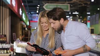Young couple choose wine at the supermarket